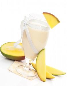 Delicious mango milk shake with fresh mango fruit isolated on white background. Refreshing summer drink.